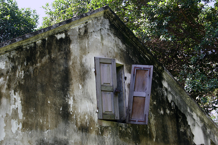 "At The Temple Of Learning In Hanoi, Vietnam Stands An Outbuilding That Has Seen Better Days And Has A Forlorn, Uncared-for Look. There Is Moss Growing On The Stucco Walls And A Shutter Hanging Off A Hinge. A Watercolor Filter Has Been Applied To The Photo To Give It A ""painterly"" Effect."